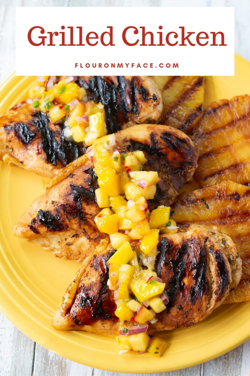 A serving plate with 3 grilled chicken breasts topped with fresh mango salsa with grilled pineapple slices in the background.