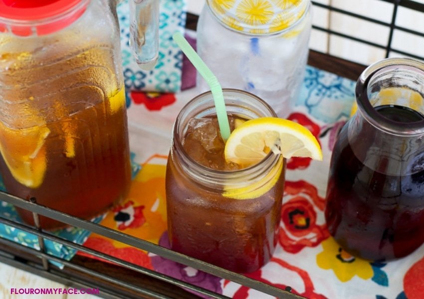 a serving tray with a pitcher of Hibiscus Iced Tea with a glass filled with tea, a lemon slice, and a straw, with a bottle of hibiscus simple syrup