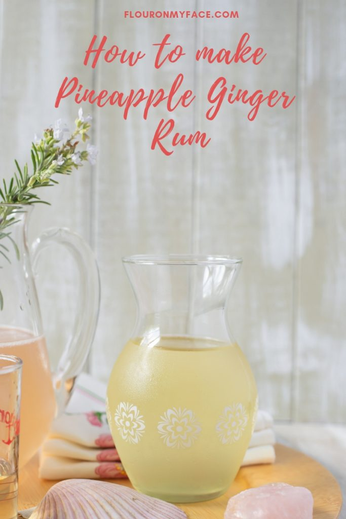 A decanter with homemade Pineapple Ginger Rum with the ingredients to make a Shell Beach Cocktail recipe