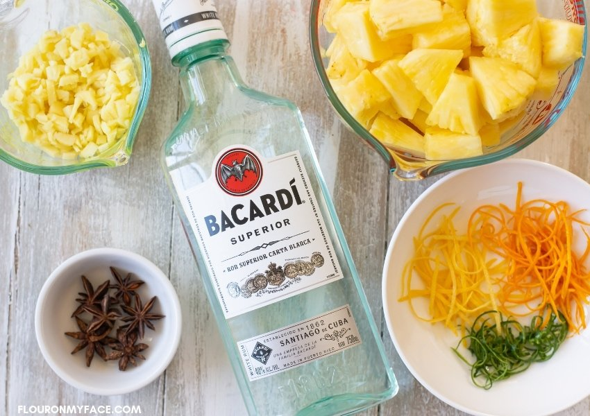 Pineapple ginger rum ingredients in individual bowls with a bottle of Bacardi white rum.