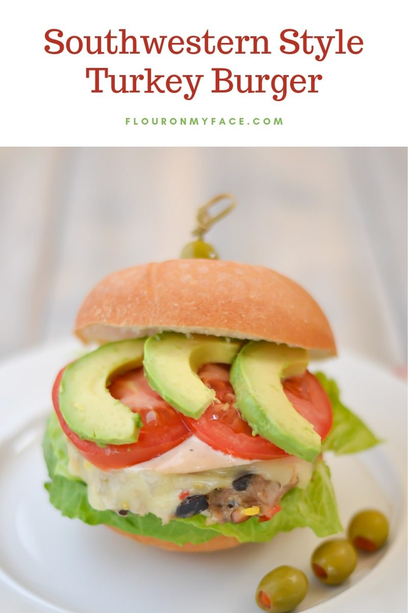 Close up photo of a southwestern style turkey burger on a bun with melted cheese, lettuce and tomato