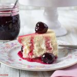 Sweet Cherry Preserves served over a slice of cheesecake with a jar of the preserves in the background