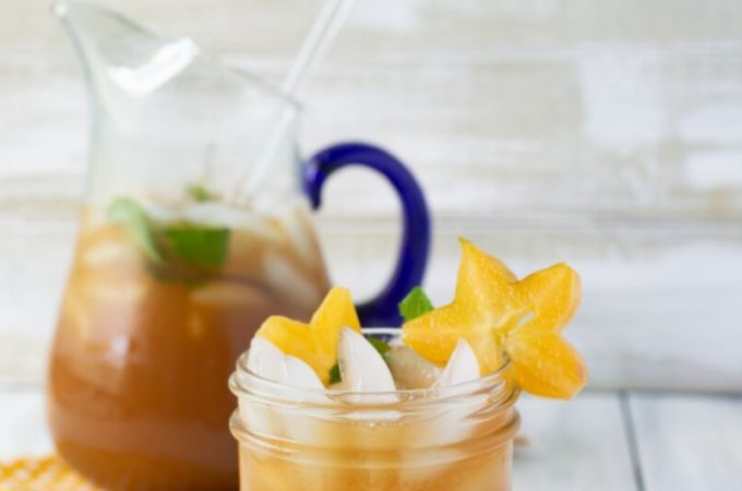 A mason jar glass filled with Carambola iced tea recipe with sliced starfruit and mint garnish. The filled glass pitcher is in the background.