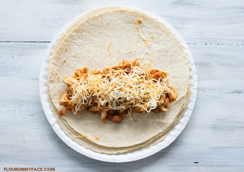 overhead photo of a paper plate with a stack of warmed flour tortillas with the top one with a portion of chicken burrito filling with shredded cheese sprinkled on top before rolling up the burrito.
