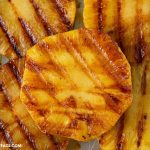 a close up photo of Chili Lime Grilled Pineapple slices on a baking tray