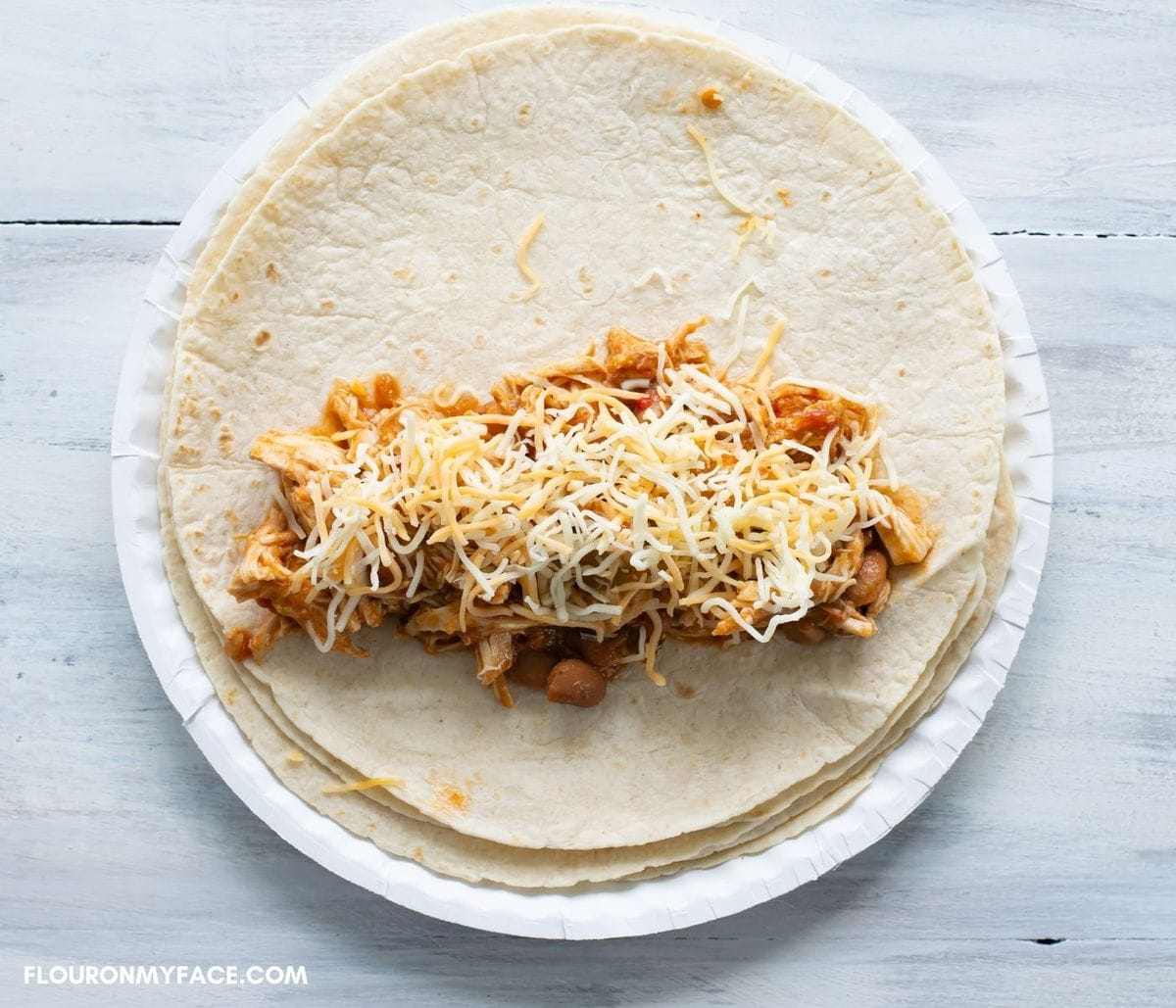 Showing how to fill a burrito.