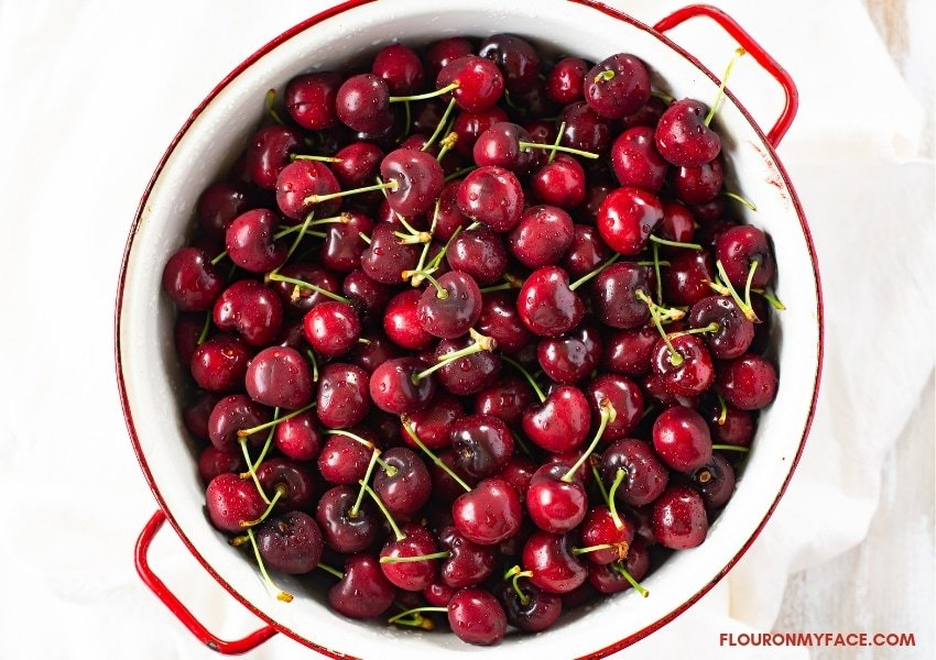 Fresh sweet red cherries in a white galvanized colander rinsed in cold water and ready to pit.
