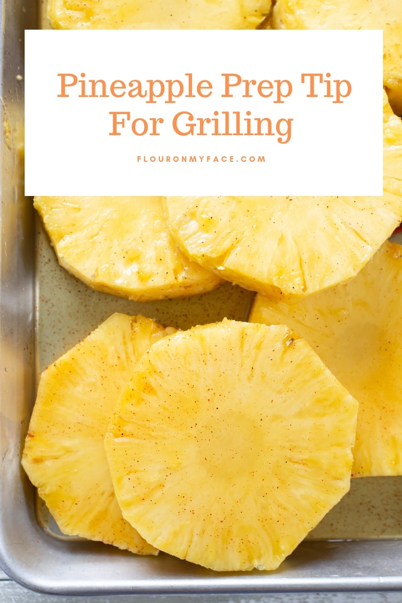Slices of fresh pineapple slices on a baking sheet and brushed with a chili honey glaze