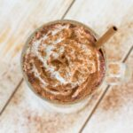 Overhead image of a mug filled with Pumpkin Spice Latte topped with whipped cream.