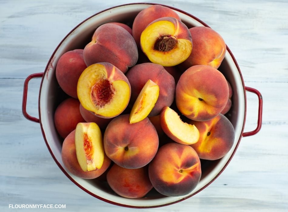 Fresh summer peaches piled high in a white enamel colander, with a few pieces of a sliced peach on top of the whole peaches.
