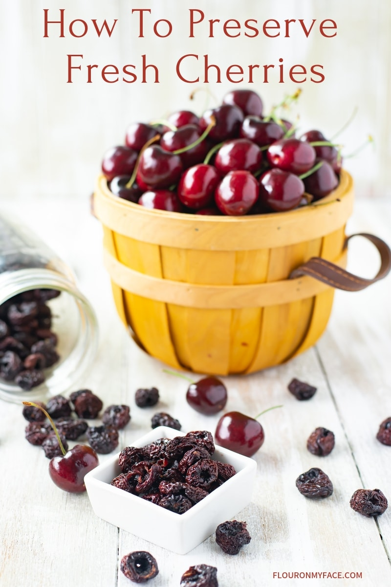 a small bowl filled with dried cherries in the background is a wooden basket filled with fresh cherries