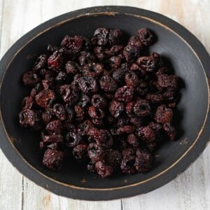 Dehydrated Cherries in a black wooden bowl.