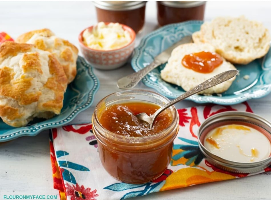 A table setting with biscuits on a plate in the background with a opened jar of thick and rich homemade Peach Honey Butter.