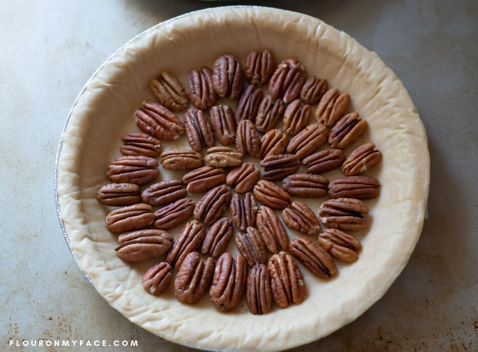 an overhead photo of an unbaked pie crust with a layer of pecan halve arranged in a pretty pattern.