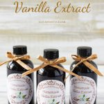 Homemade Vanilla Extract in clear 4 oz bottle decorated with a free vanilla label and tied with a bow at the top