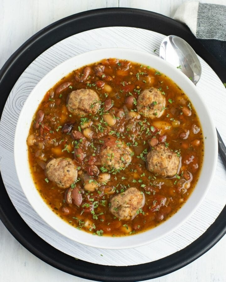 A white bowl filled with Italian Bean Meatball Soup.