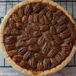 Overhead photo of an uncut freshly baked pecan pie.