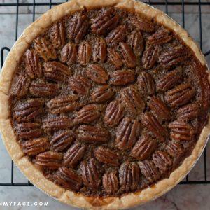 Overhead photo of an uncut freshly baked pecan pie.