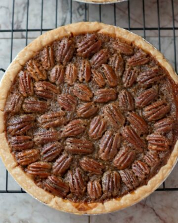 A homemade pecan pie on a wire rack cooling.