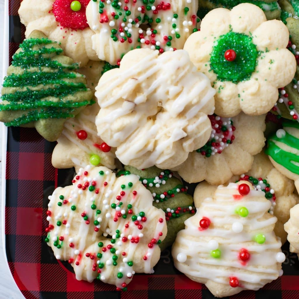A holiday plate with a pile of the Almond Spritz Cookies Recipe for a cookie exchange or office Christmas party showing the different ways you can decorate Spritz cookies for Christmas.