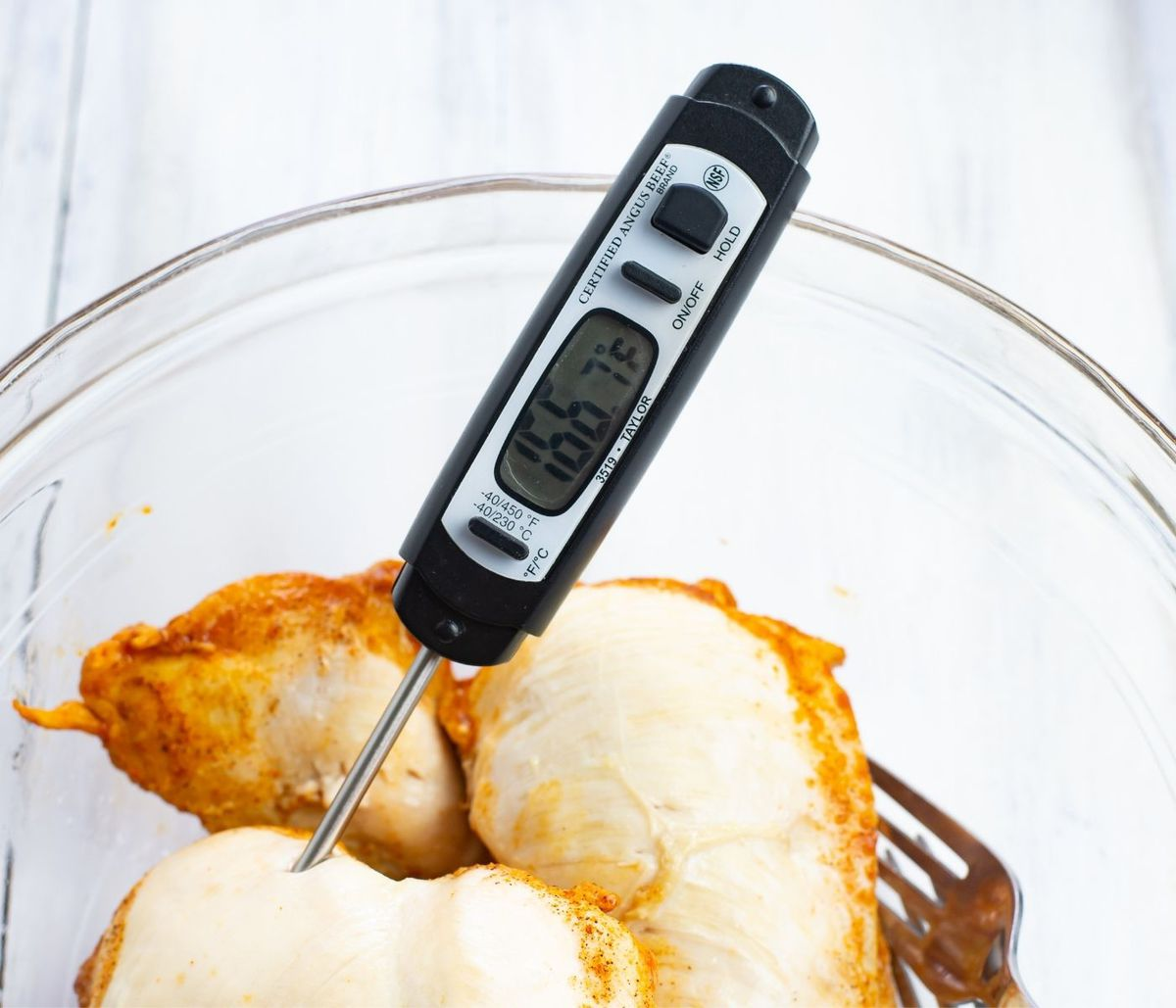 An instant read thermometer checking the internal temp of cooked chicken.