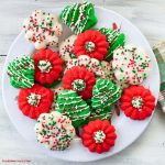 red, green and white Cream Cheese Spritz Cookies decorated with a powdered sugar glaze and Christmas sprinkles