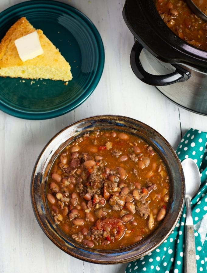 Crock Pot Cowboy Bean Soup in a bowl with a piece of cornbread in the background.
