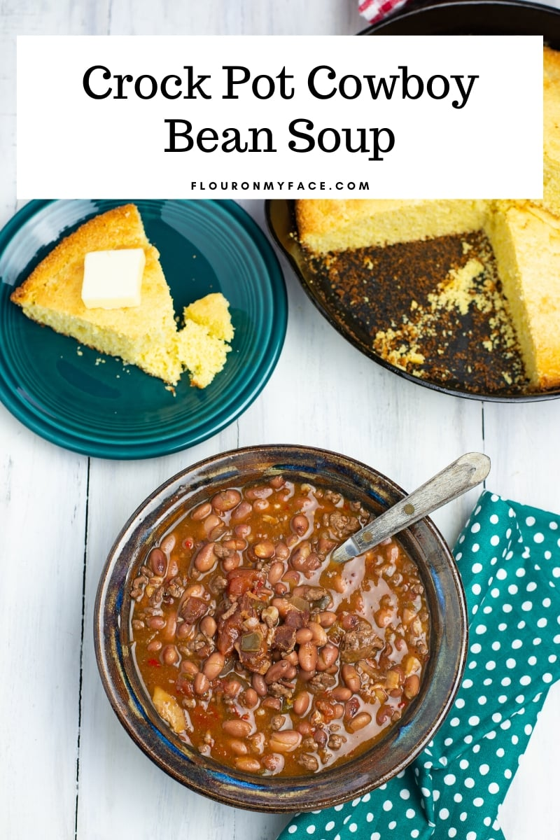 Overhead photo of one serving bowl of Cowboy Bean Soup with a iron skillet of freshly baked cornbread. The Crock Pot Cowboy Bean Soup recipe made with ground beef.