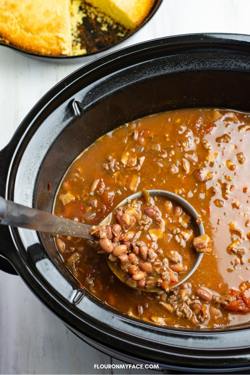 Image of a ladle scooping a helping of Crock Pot Cowboy Bean Soup up to fill a bowl