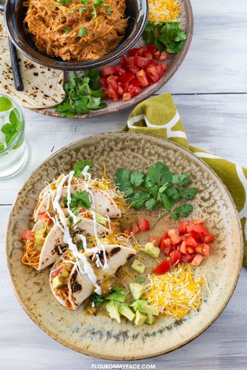 Overhead photo of a brown speckled dinner plate with 3 chicken tacos, diced tomatoes, diced avocados, fresh cilantro leaves make with the Instant Pot Creamy Chicken Tacos recipe