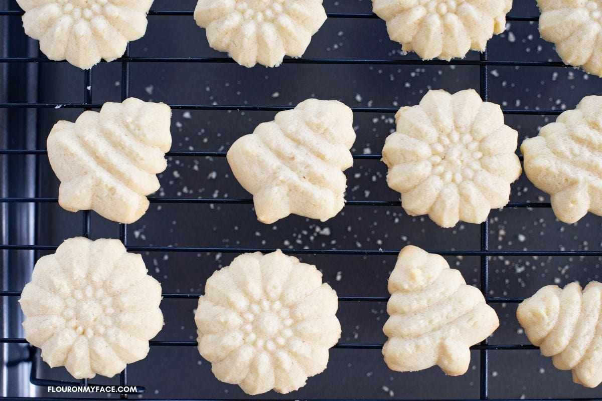 Baked spritz cookies on a wire cooling rack.