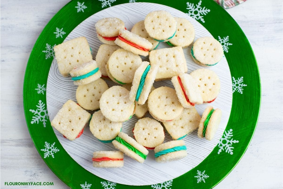 Christmas sandwich cookies on a holiday plate.