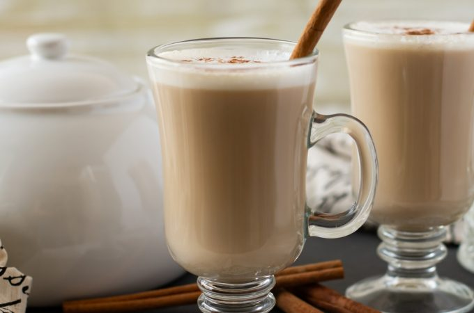 A mug of Crock Pot Chai Latte topped with frothy milk. cinnamon and garnished with a cinnamon stick. A white tea pot is in the background