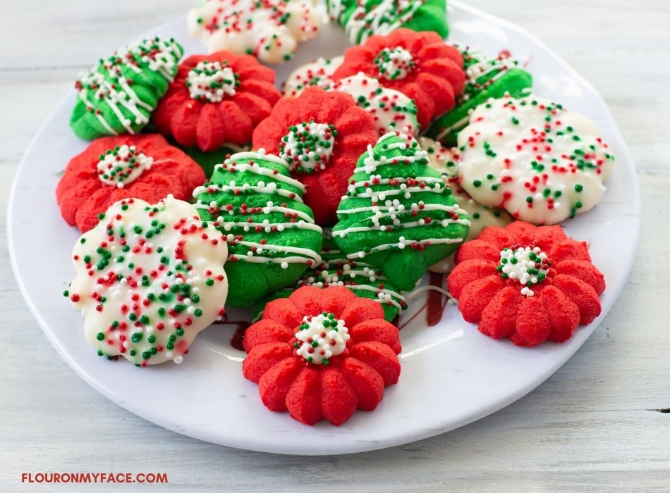 Red, green and white colored Cream Cheese Spritz Cookies on a holiday plate decorated with sprinkles and cookie sugar