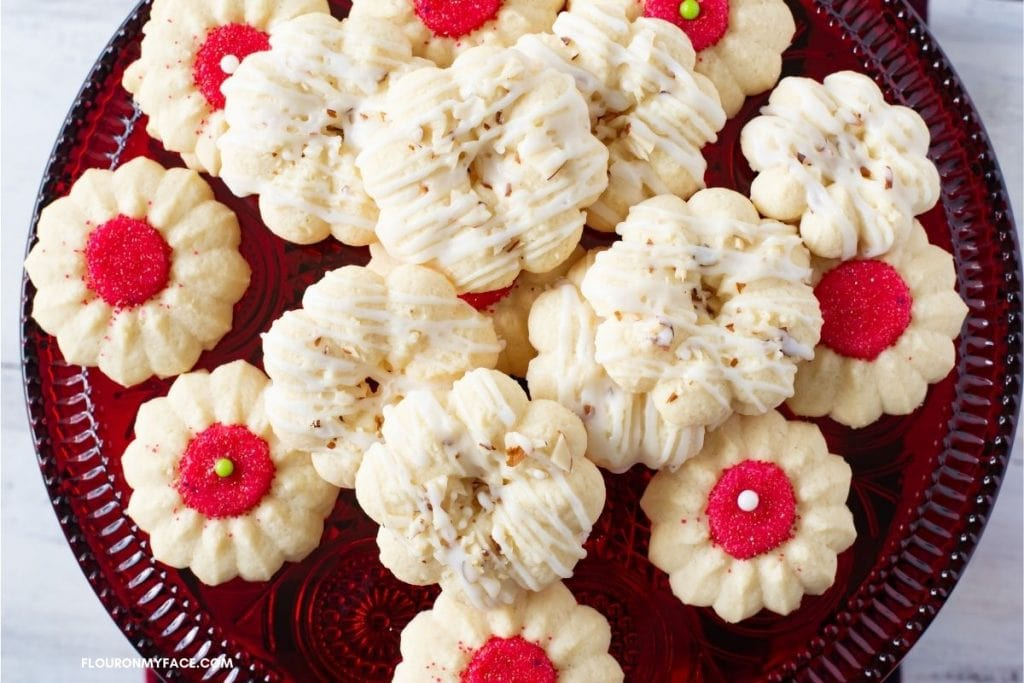 decorated spritz cookies on a red glass cake stand.