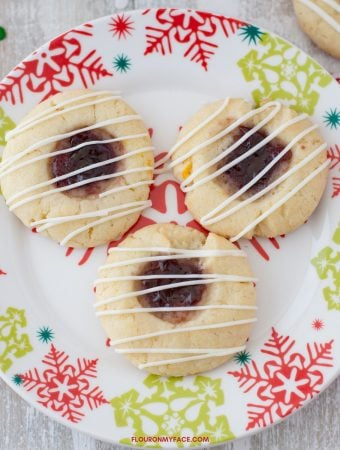 A holiday plate with 3 Raspberry Thumbprint cookies with a white chocolate drizzle.