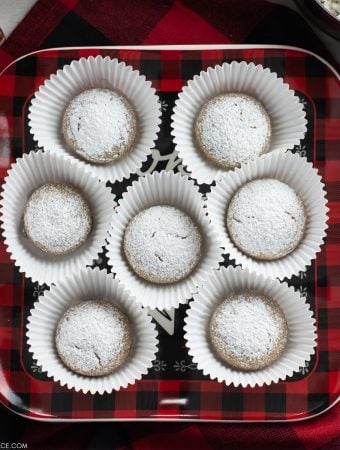 A black and red plaid Christmas plate with homemade German Spice Cookies in muffin papers on a Chrstmas dessert table.