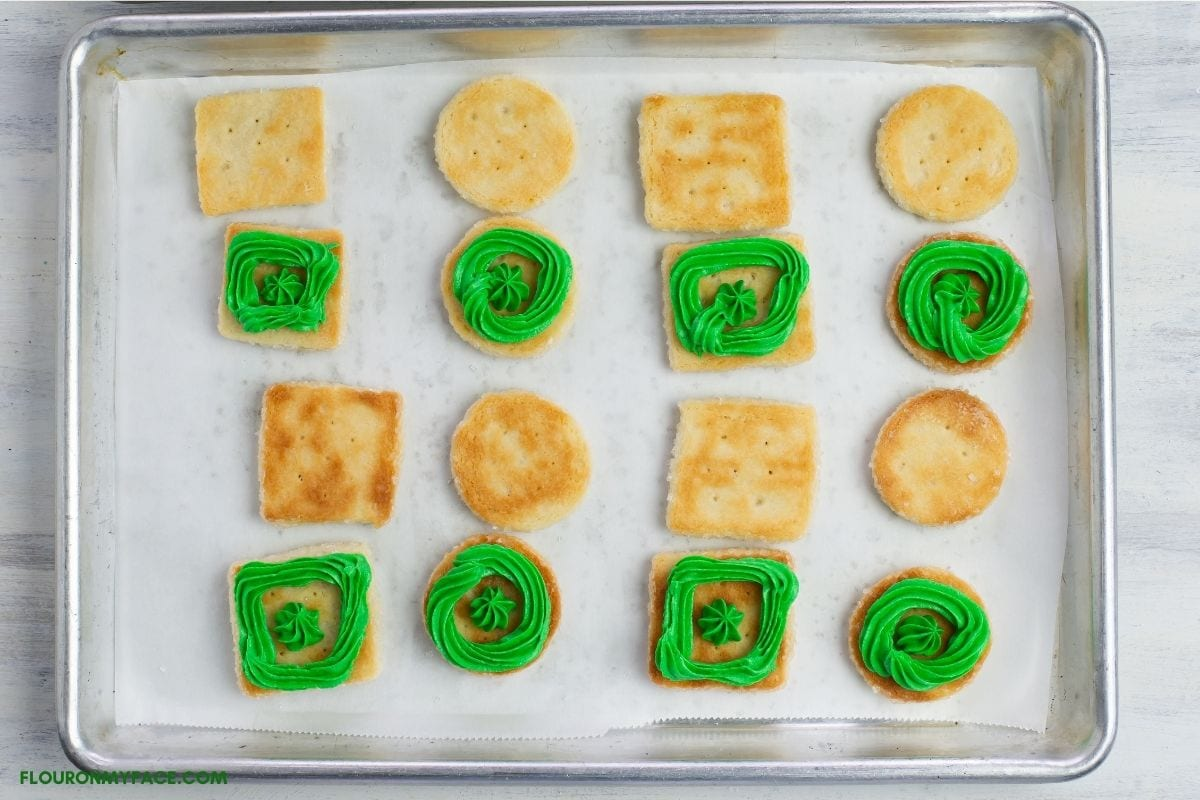 Filling sandwich cookies with green buttercream filling.