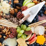 Overhead closeup photo of a holiday cheese platter with cheese, meats, crackers and nuts
