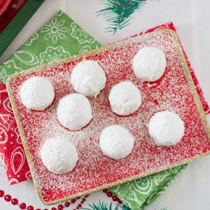 Mexican Wedding Cookies on a red holiday plate.