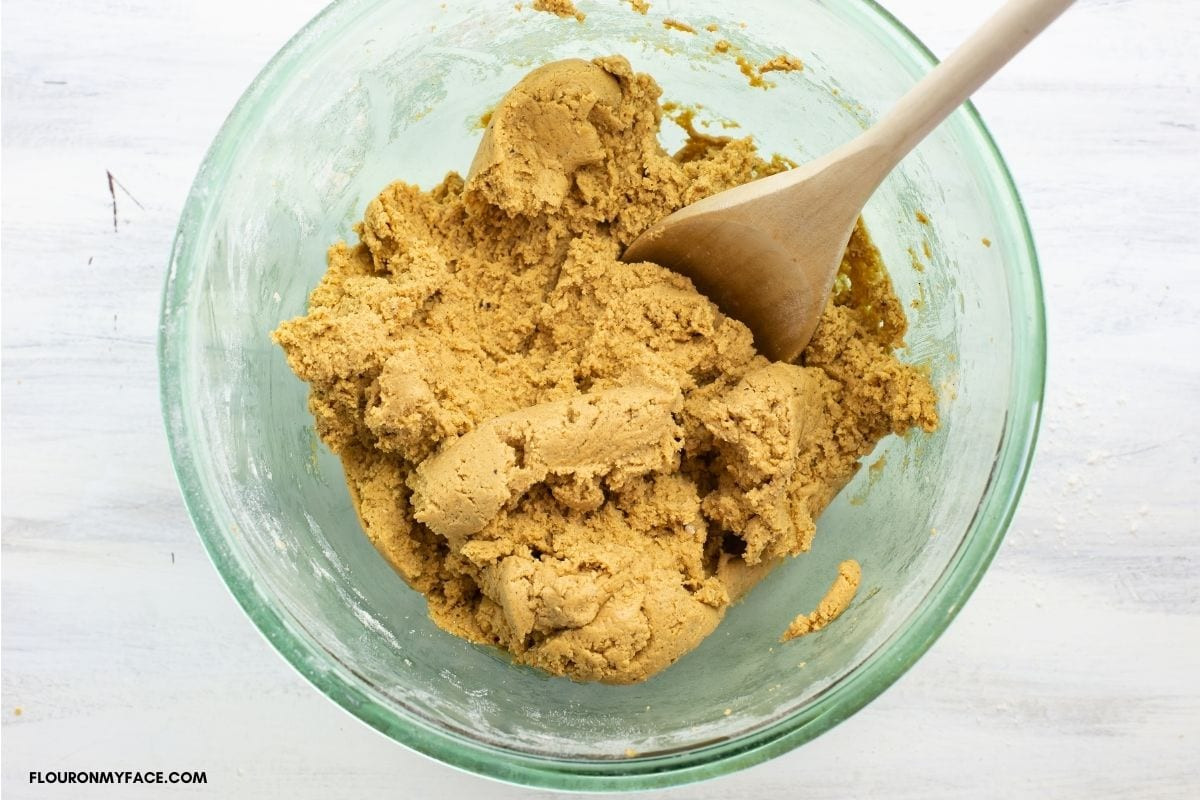 Mixing cookie dough with a wooden spoon.