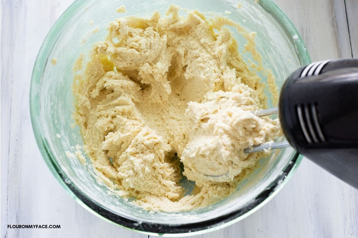 Very thick Spritz cookie dough with a mixer in the bowl.