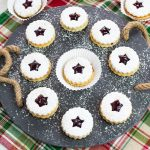 Raspberry Linzer Sandwich Cookies on a slate serving platter