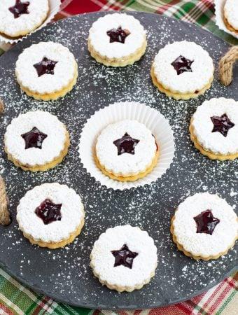 Raspberry Linzer Sandwich Cookies on a slate serving platter