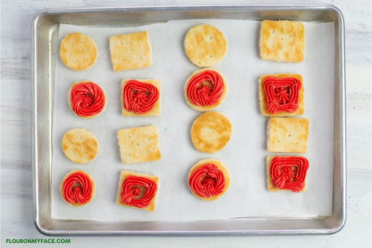 sandwich cookies are a cookie tray being filled with frosting.