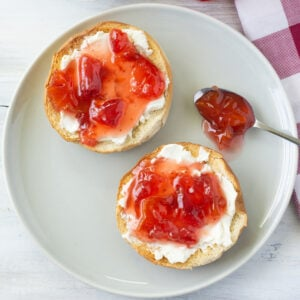 Homemade Carambola Strawberry Jam spread over a toasted bagel with cream cheese