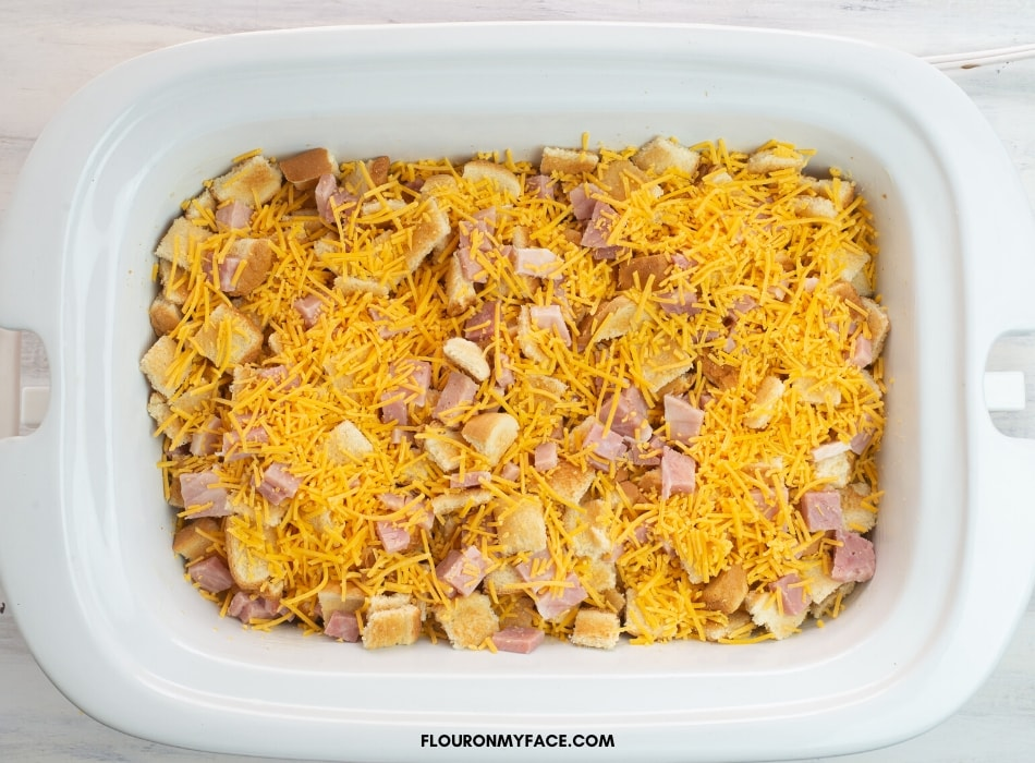 Overhead photo of a casserole crock pot filled with the ingredients to make a ham and egg breakfast casserole