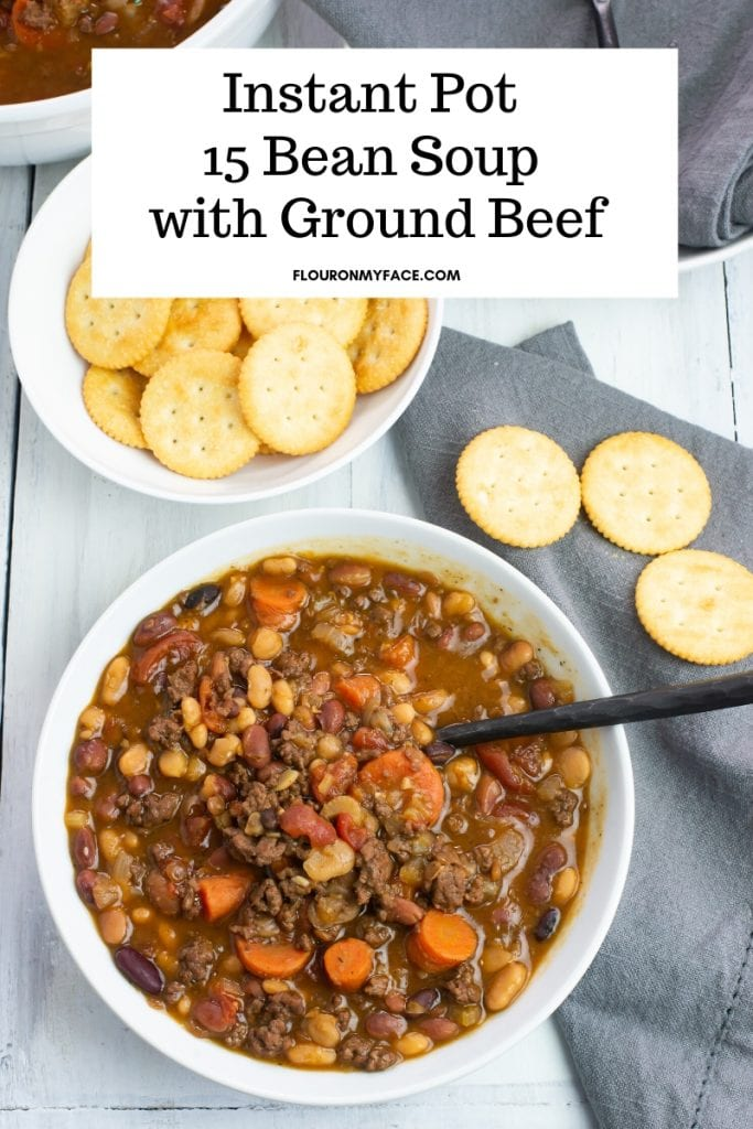 A white soup bowl filled with Instant Pot 15 Bean Soup recipe made with ground beef. A bowl of crackers and a grey cloth napkin are also on the table.