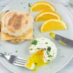 A serving of Instant Pot Poached Eggs on a plate with orange slices.