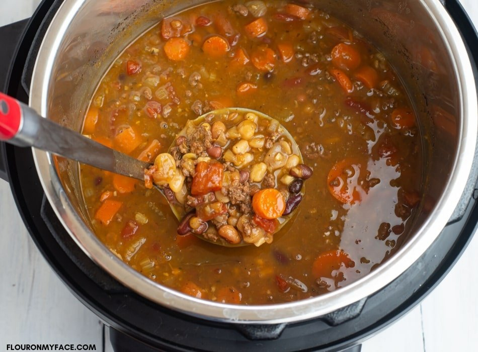 A metal ladle filled with Instant Pot 15 Bean Soup